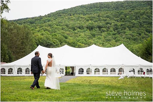43_bride-groom-hold-hands-walking-toward-white-reception-tent