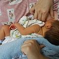媽媽用毛巾捲推寶寶的背  頭後仰下巴貼乳房.JPG