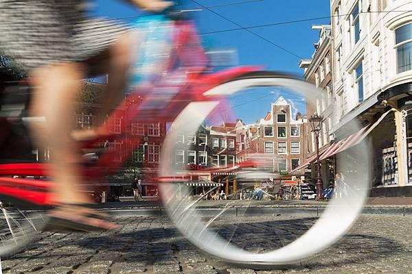 一個單車騎士正享受地在阿姆斯特丹的巷道中穿梭