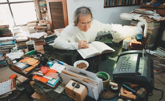 南方朔盤坐在閣樓的小茶几前寫作,貓咪球球是書僮,連書桌都有牠的位置。記者黃義書/攝影