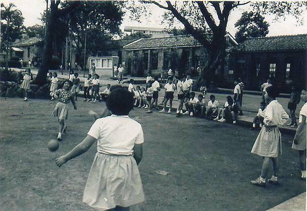 下課時在校園玩耍---背景是用唭哩岸石建造的一至六年級教室.jpg