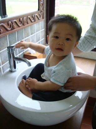 這小孩很愛洗手台