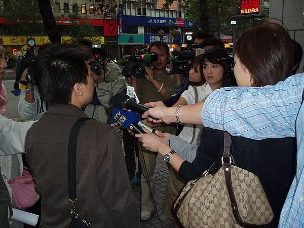 記者採訪中,背對鏡頭者為台中上來的郭先生